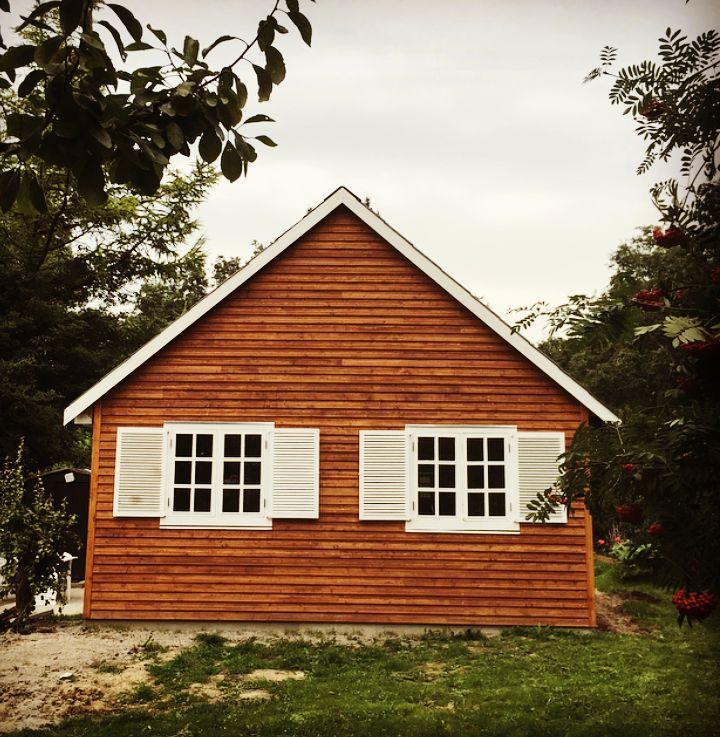 Huset set forfra færdigbeklædt med nymalede  skodder.  #kolonihavehus