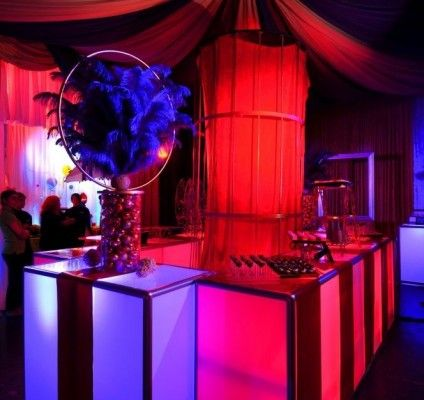 Big Top #decor for serving up #food and #beverage. Love the big #purple #feathers and the #cage in the centre! #event #red #brightideas #events #eventlighting #tent #circus #bigtop #celebration