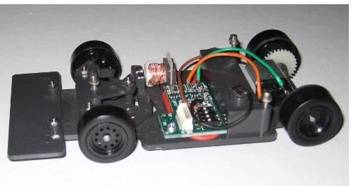 A Magracing chassis complete with radio gear.   Up to 16 cars can be raced at the same time using easily switched channels. Battery is inserted from under the car, allowing 3 second pit stops!