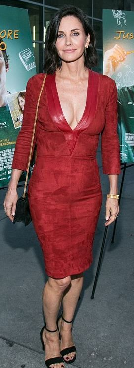Who made  Courtney Cox's red suede dress and black chain handbag?