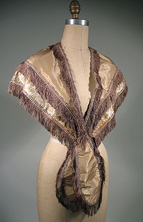 This tan silk taffeta pelerine dates from the 1860s, possibly the late 1850s. It has a cream and gold fancy woven ribbon edge, with brown silk fringe along the edges and covering the join of the ribbon to the silk. It is lined in a lightweight cotton. There are no closures.