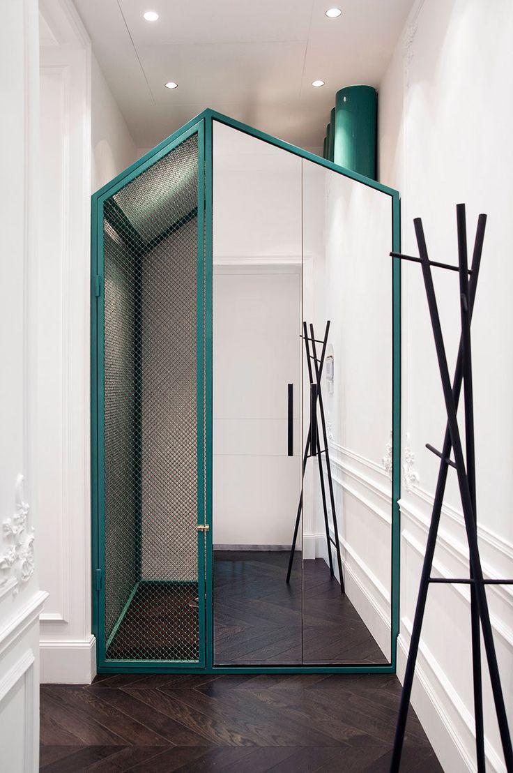 При входе в эту квартиру есть небольшой бирюзовый дом.  Зеркальная часть дома является шкаф и за шкафом есть личное пространство для собаки дома.  Также скрытые является блок вентиляции и цветные трубы вы можете увидеть, являются вентиляционные трубы, которые идут к потолку.