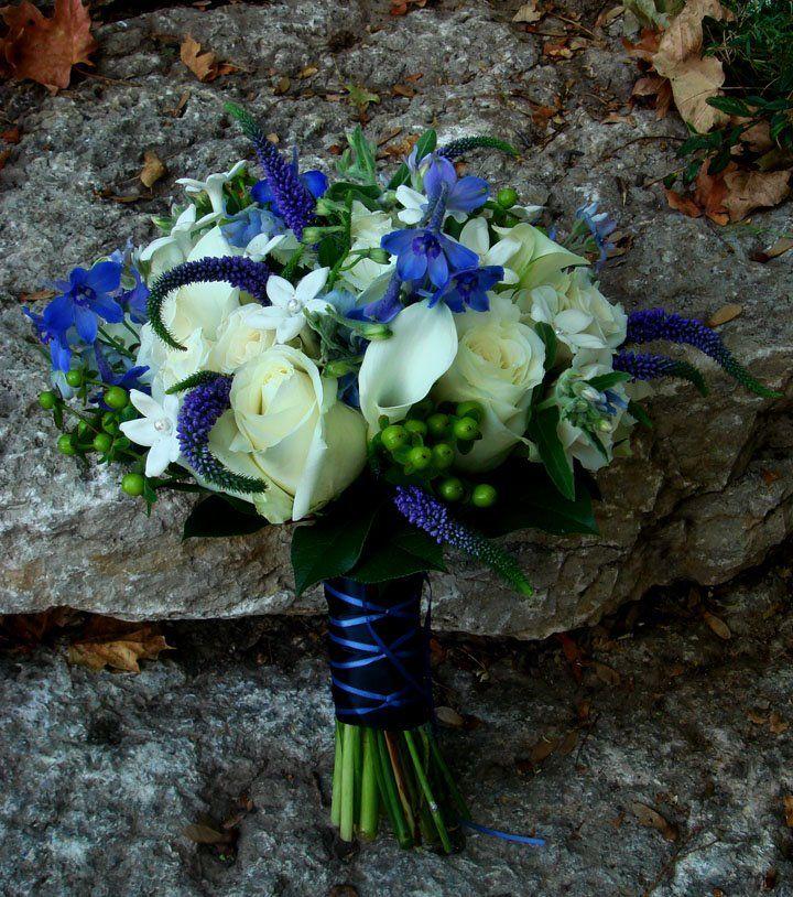 White rose, stephanotis, calla bouquet with blue belladonna delphinium, veronica and green hypericum.