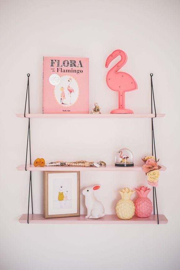 Une étagère avec un flamant rose, des livres et une veilleuse lapin + ananas