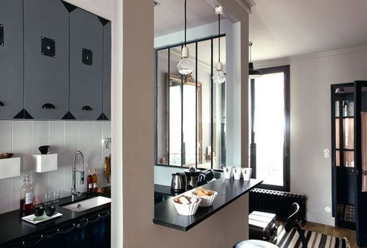 An open kitchen with a bar area in a small flat in paris