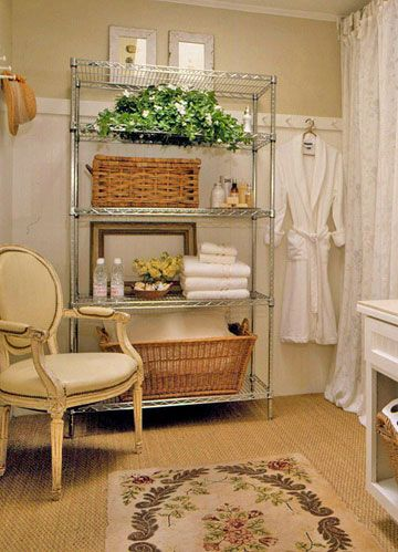 A restaurant-style steel shelf unit turns an open wall into storage for towels, washcloths, and shower supplies.