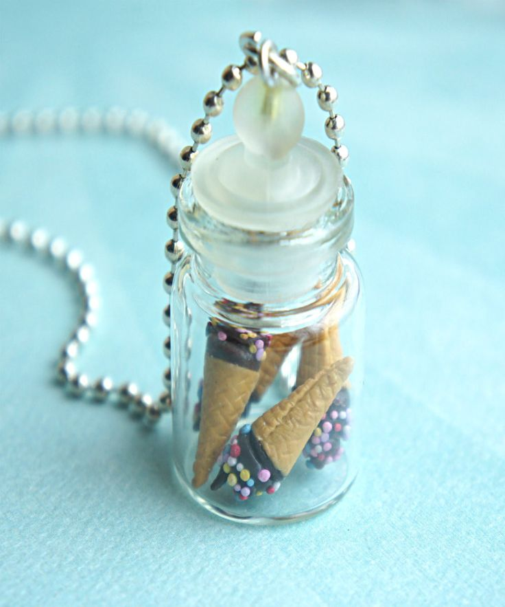 This necklace features a glass jar pendant of handmade ice cream cones sculpted from polymer clay. The glass jar measures about 2.5 cm tall and is securely attached to a silver tone ball chain necklac