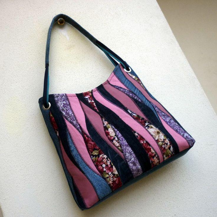 džíska něžně romantická Větší kabelka je ušitá ze středně modré rercydžínoviny. Přední strana je kompozicí materiálů v odstínech růžové, fialové, béžové a červené , doplněnou zajímavě probarvenými kousky modré džínoviny. Stejný motiv v zjednodušené podobě se opakuje i na zadní straně kabelky. Dalším zdobným prvkem je složené ucho z modrého a ...