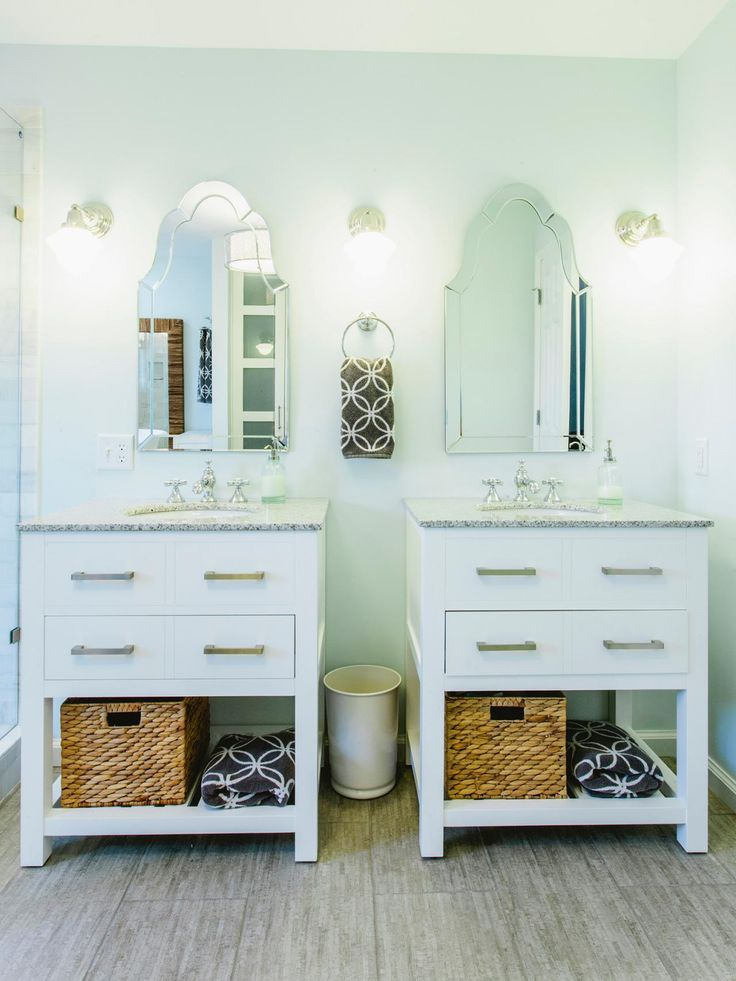Two single vanities were used to give the owners a double vanity area without the bulk of a double vanity piece. In addition to the vanity storage, a woven basket sits on a shelf under each.