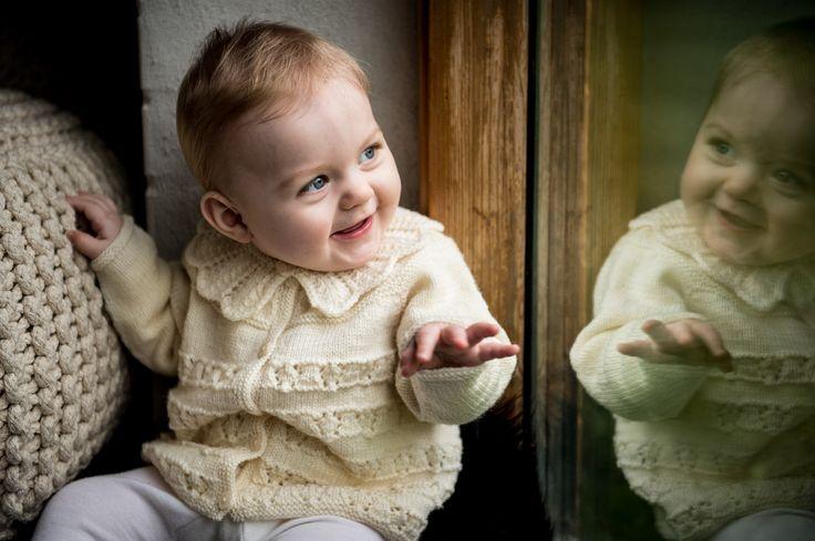 129/5 Feminin baby trøje med bærestykke. Strikket i Mayflower Easy Care. Køb opskriften i din lokale Mayflower Forhandler.