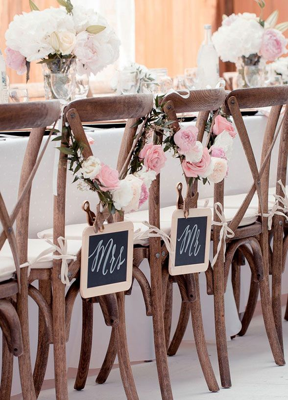 Whether you're planning on sitting at a sweetheart table or with your wedding party, a statement-making chair back is an absolute must for your reception. Take a look at our favorite ways to dress up your bride and groom chair backs.