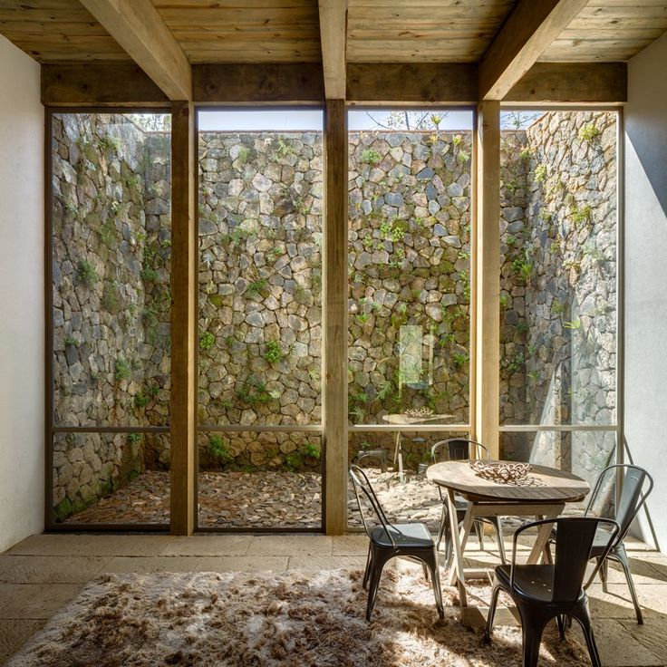 CC Arquitectos used weathered stone, natural wood and huge panels of glazing to create this secluded woodland house in Mexico's scenic Valle de Bravo region.