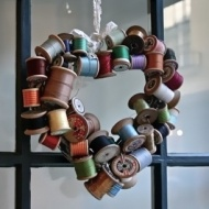 I have a container full of my great grandma's thread spools.  Love this idea!