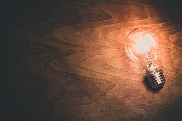 Photographie d'une ampoule allumée sur un planche de bois.