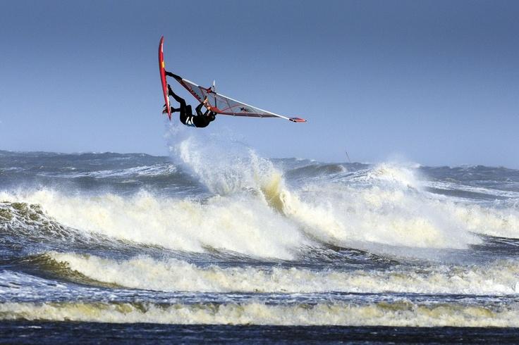 Een surfer geniet van de harde wind en hoge golven op het strand van scheveningen waar de storm langs raast.