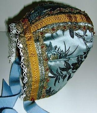 Luen er i dueblå mønstret silkebrokade. Fôret er av bomull. Bomullsblonde,gull kniplingsblonde, perledekor og fløyels- og ripsbånd. Håndsøm. Denne luen ...