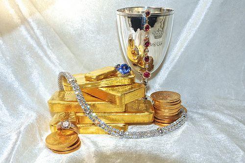 Lingotti in oro, monete, colier in diamanti, rubini, zaffiri e coppa reale d'argento