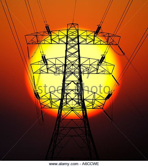 A High Voltage Pylon against a Glowing Sun - Stock Image