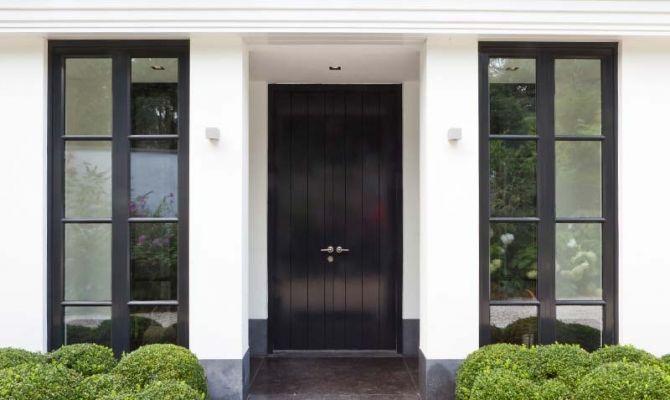 Luxe tijdloze uitstraling bij een wit pand, donkere raamkozijnen en een donkere voordeur.