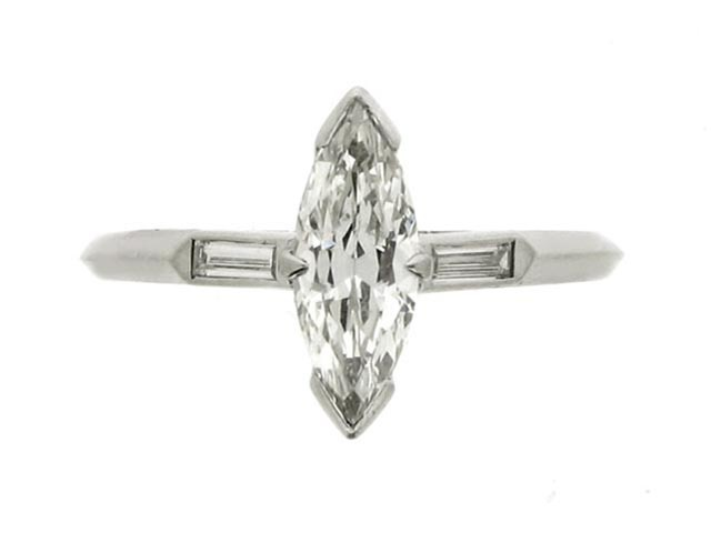 Marquise shaped diamond ring, circa 1940. A platinum and iridium ring set with one central marquise shaped old cut diamond in a claw setting with an approximate weight of 0.75 carats, flanked by raised shoulders set with two rectangular baguette cut diamonds in rubover collet settings with an approximate total weight of 0.10 carats, on a knife edge shank, and with an approximate combined diamond weight of 0.85 carats.
