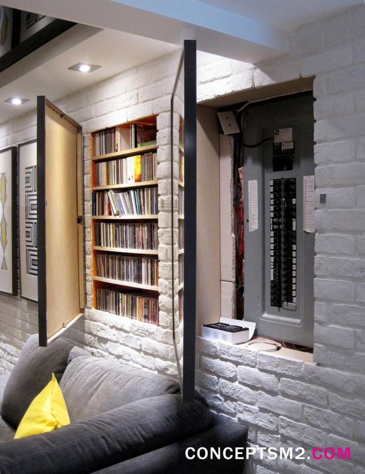hidden fuse box and media storage in wall hidden by hinged art frames for basement remodel