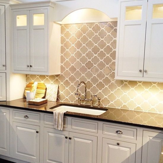 Gorgeous kitchen with white cabinets with polished nickel hardware alongside black quartz countertops and a pale gray arabesque tiled backsplash. The undermount kitchen sink pairs with a gooseneck bridge faucet below upper cabinets with glass detail.