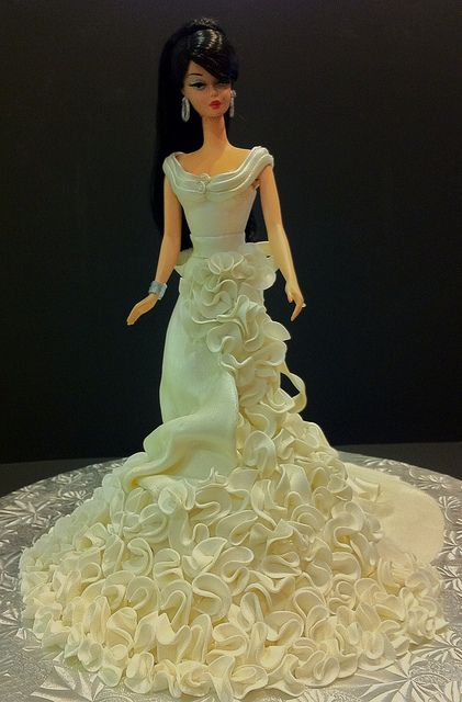Barbie The Wedding Dress Cake, Silkstone Barbie from Fashion Model Collection. Flared portion of skirt is cake to feed 4-6 ppl. Dress is made of draped rolled fondant and a cascade of handmade ruffle flowers. Jewelry is royal icing with crystal sugar accents.