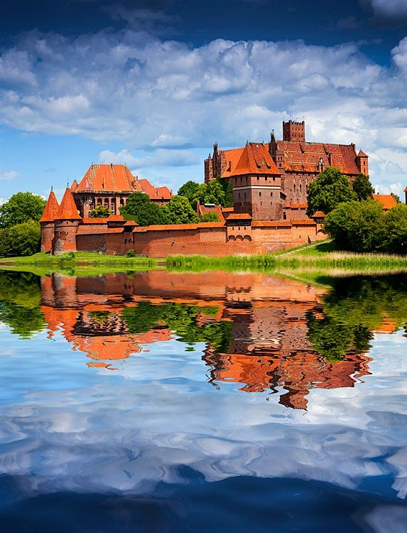 """Castle in Malbork was built in Poland (Prussia) by the Teutonic Order as an Ordensburg. The Order named it Marienburg, literally """"Mary's Castle"""". The town which grew around it was also named Marienburg, but since 1945 it is again, after 173 years, part of Poland and known as Malbork. The castle is a classic example of a medieval fortress, and is the world's largest brick gothic castle."""