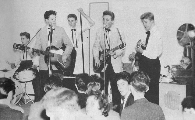 The First Photograph of Lennon and McCartney Together, November 23, 1957    The Quarrymen, 1957. The first known photograph of John Lennon and Paul McCartney performing together, as part of the Quarrymen. From the left: Colin Hanton drums, Paul McCartney guitar, Len Garry tea chest bass, John Lennon guitar, Eric Griffiths guitar.    New Clubmoor Hall, Broadway, Liverpool.    Photographer: Leslie Kearney