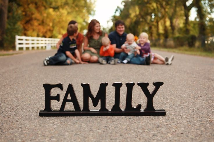 """Make it a fun shot where they are all """"sitting""""on it or posed around the words family from the distance so they look tiny"""