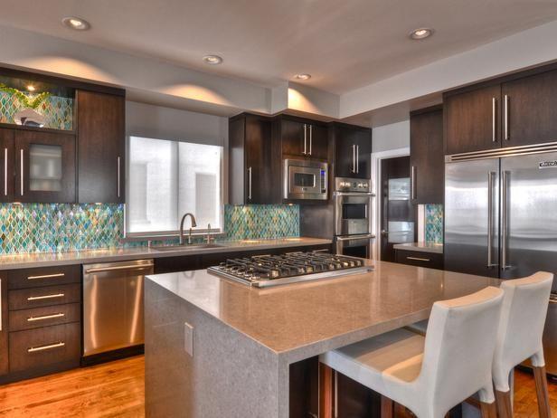 Kitchen with grey quartz island; the diamond-shaped sea green back splash tiles are interesting alongside dark brown contemporary cabinets.