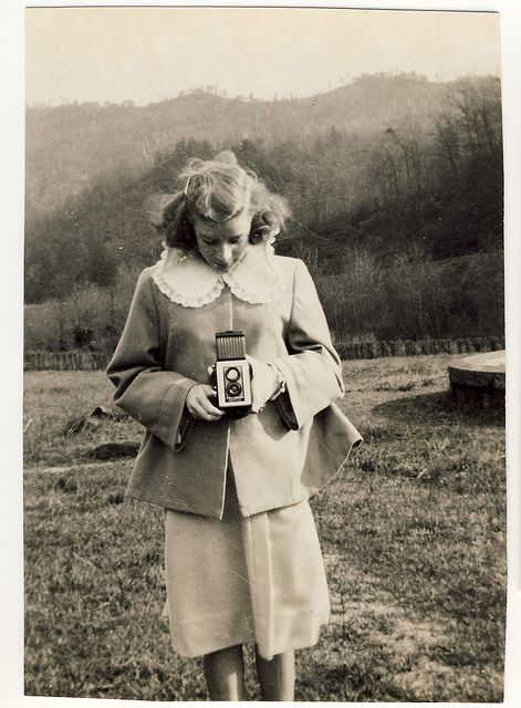 holding a vintage camera. love the oversized collar.