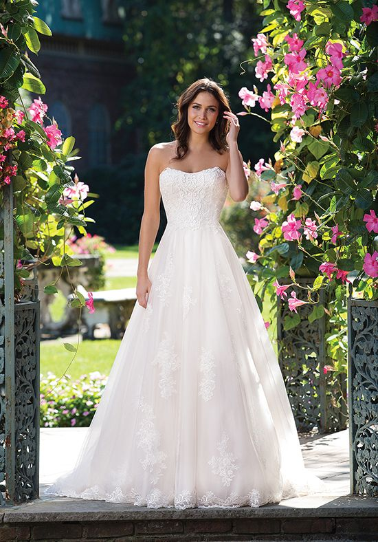 Embroidered and corded lace appliques adorn this strapless tulle ball gown. This figure flattering style has a natural waist, hem lace, and a chapel length train.