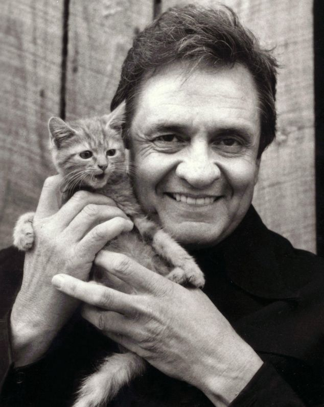 Johnny Cash is holding a kitten.