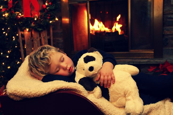 DIY Christmas card photo idea: child sleeping in front of fireplace with toy.