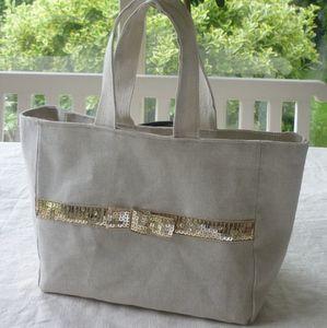 Sac en toile écrue avec petit noeud paillettes dorées sur une face et ruban paillettes sur l'autre face. www.laurence-raulet.com