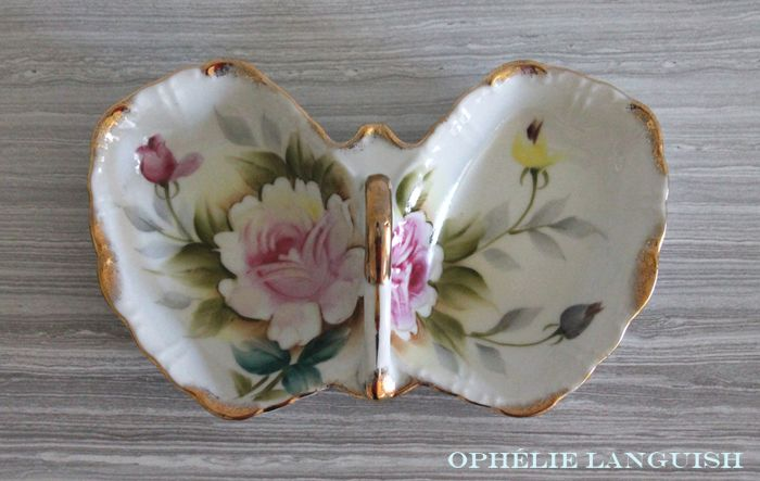 Gorgeous hand painted porcelain butterfly shaped dish featuring beautiful pin and yellow roses. Gold trim on scrolled handle and edges. Divided into two sections. Would be perfect for serving nuts or candy, or on a vanity table for holding jewellery and trinkets.