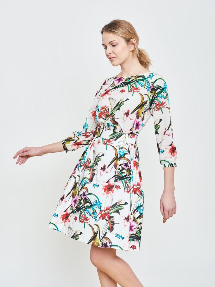 Jasna sukienka w kolorowe kwiaty. Fason rozkloszowany z zakładkami na tiulu. Dekolt łódka, rękaw długi. Długość do kolan.