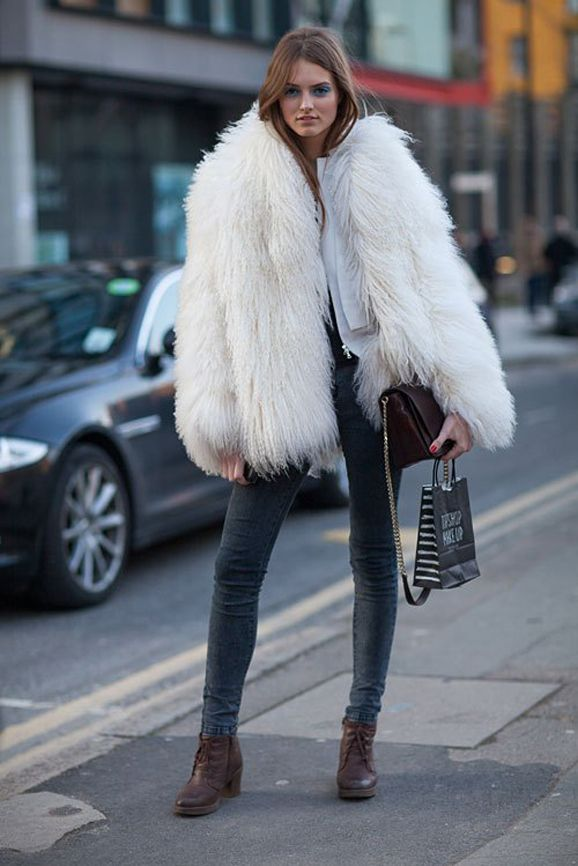 6 ways to look stylish when it's FREEZING outside - embrace fur (or faux fur) // Model-Off Duty snapped wearing a white shaggy fur coat worn with skinny jeans + lace-up brown leather ankle boots.