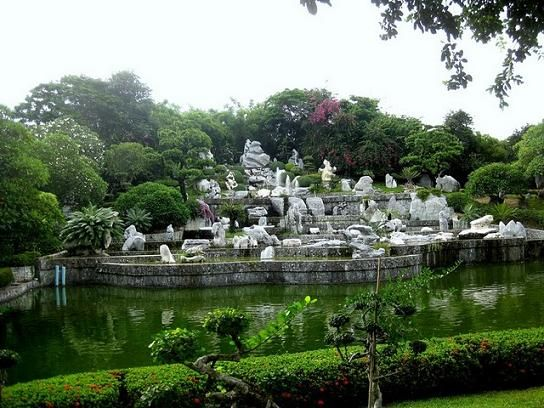 View of the Stones and Shrubs across the Lake at the Million Years Stone Park in Pattaya, Thailand