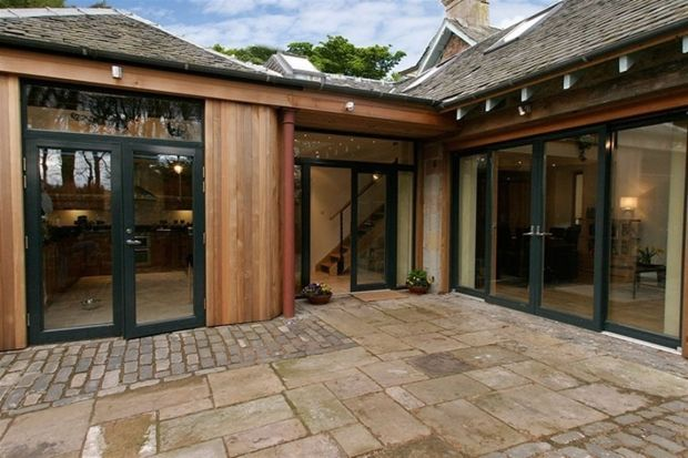 love the wood cladding and dark aluminium doors. Also like the slight overhang of the roof (we'd have it a little bigger) and the stone is nice and traditional.