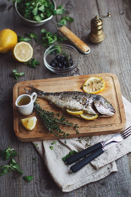fish, lemon, fresh herbs, cutting board