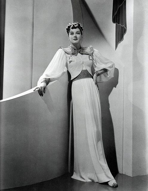 """Rosalind Russell wearing an unused Adrian design for """"The Women"""", 1939. Russell is rarely seen in conventional pin-up photos since the studios thought she didn't have the right body for it."""