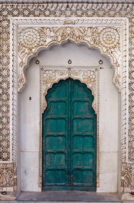 The color combinations, the carvings on the wall outside the inset lintel, and the shape of the doors themselves. Doorway, Morocco.