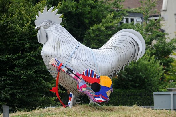 A guitar is the latest creation of Dorking's 'guerrilla knitters' to appear on the cockerel at the Deepdene Roundabout.