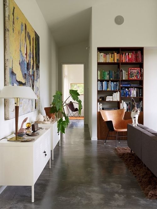 Love the concrete floor. The books organized by color is interesting too... Wonder if the librarian in me could do that?