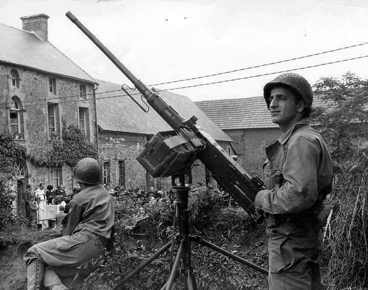 American soldiers with Browning M2HB machine gun in a town in Normandy France 1944.