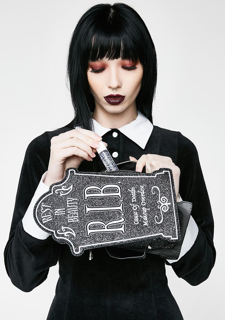 Current Mood Rest In Beauty Cosmetic Case cuz even in the coffin' your look is fire. This glittery black cosmetic case has a tombstone shape, handle on the side, and a zipper closure.