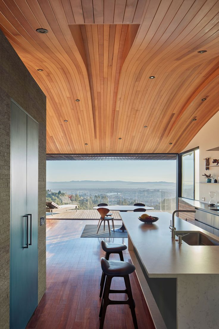 This modern home has a curved wood ceiling, The long sections of wood help to elongate the interior and draw your eye to the balcony and view.