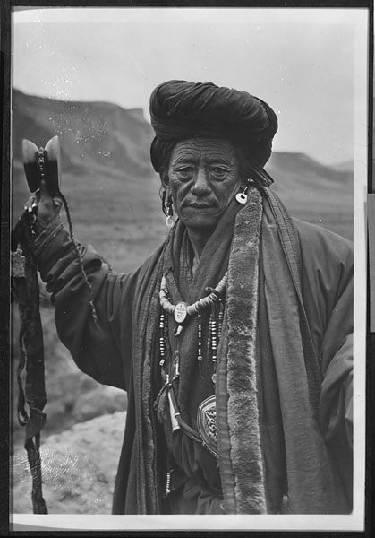 Bonpo lama with earrings, beaded necklaces, and hand drum in a state of trance. 1926, by Joseph Rock on the roof of his quarters at Radja Gomba. According Rock's diary, the sorcerer is from the Nyimaha or Red Sect. He is a member of the Konser tribe belonging to the five Hor states. The sorcerer's name is Tsepten-ja.